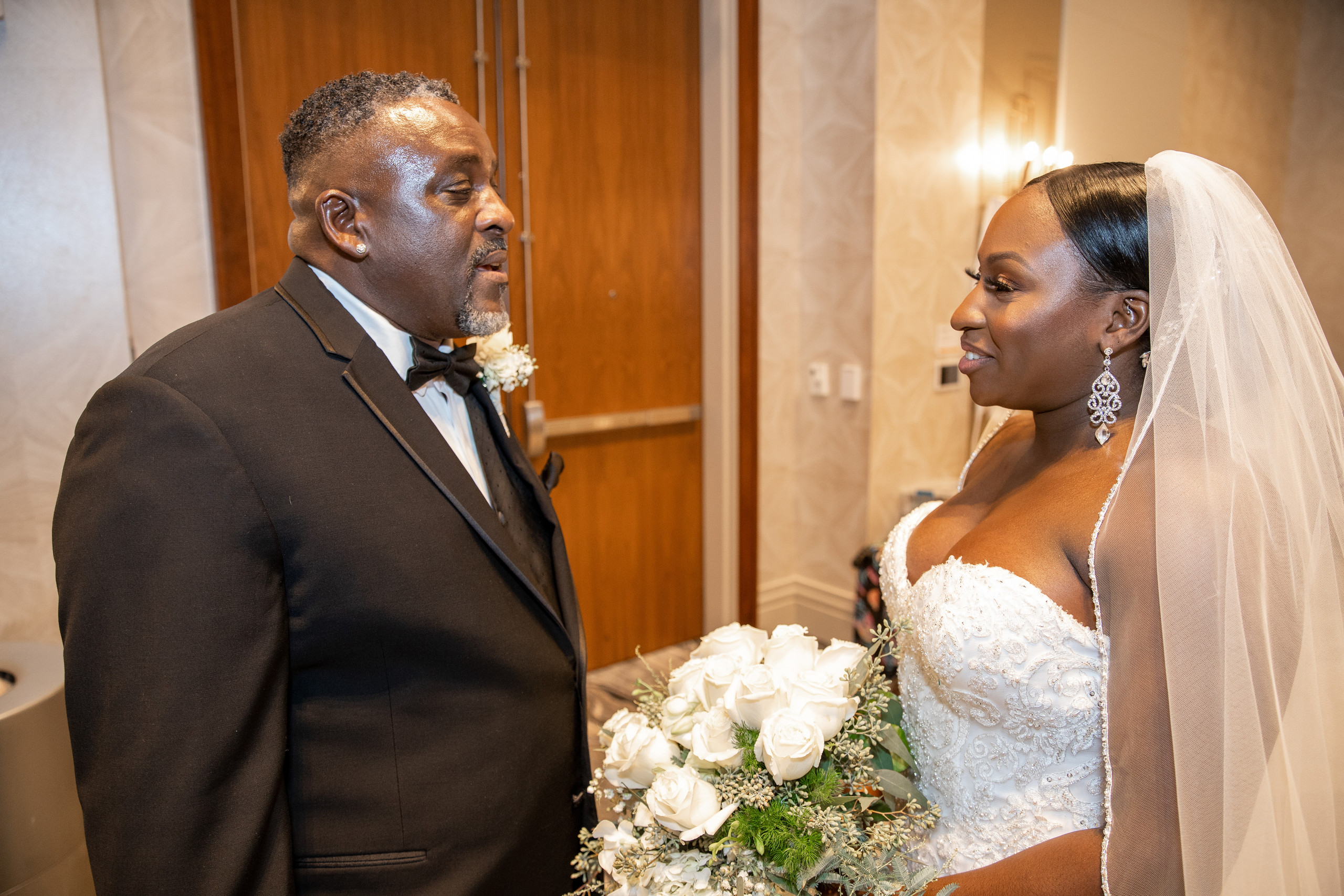 The father of the bride sees his daughter for the first time before the wedding ceremony at the Hilton Main in Norfolk, Virginia.