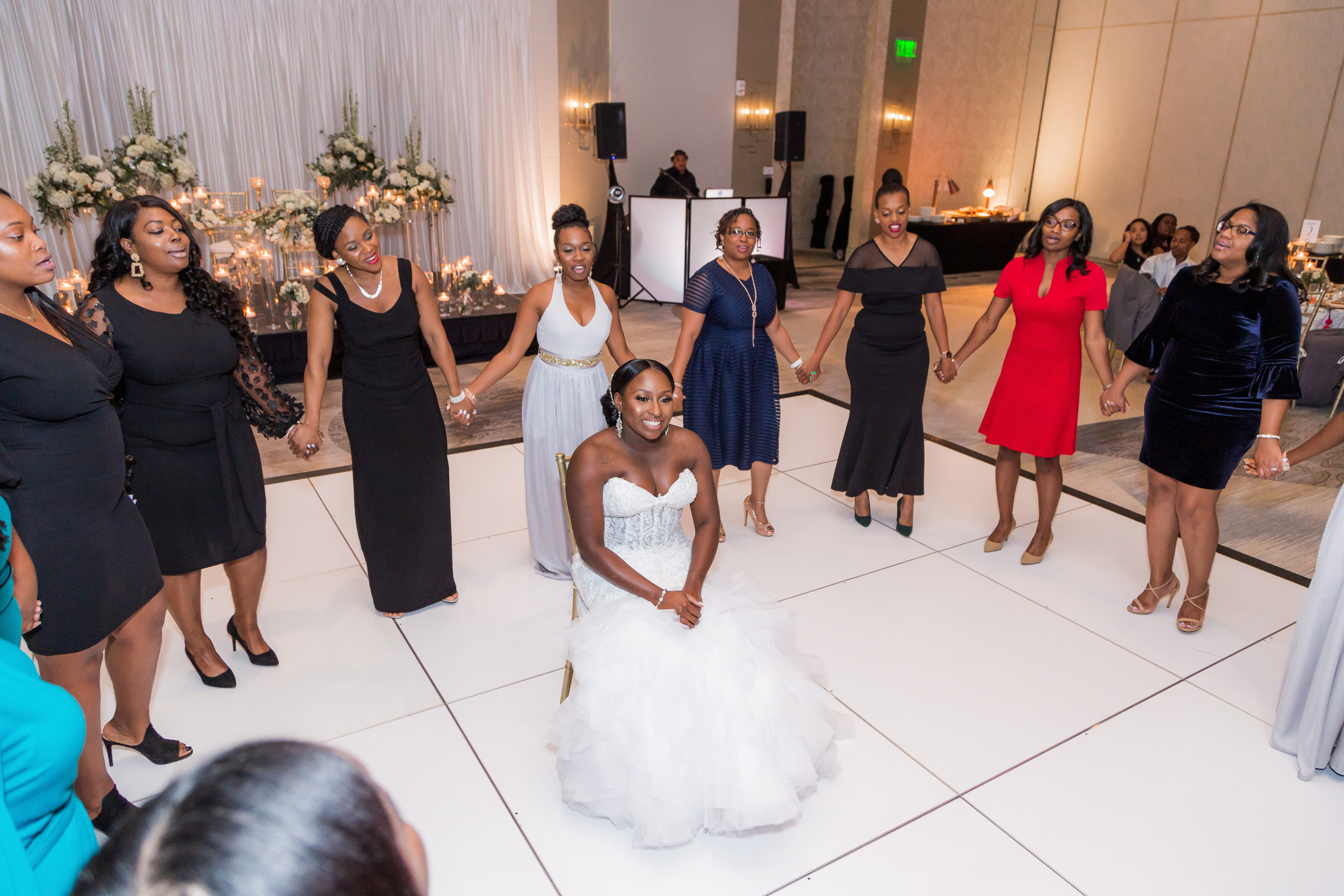 The ladies of Delta Sigma Theta Sorority Incorporated saranade the bride on the dancefloor during the wedding reception at the Hilton Main in Norfolk, Virginia.