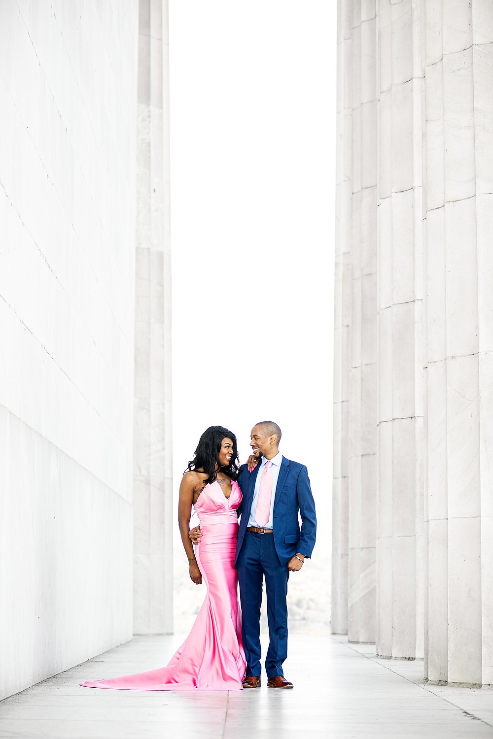 Beyonka and E'an walking along the Lincoln Memorial columns during their engagement session in Washington DC.