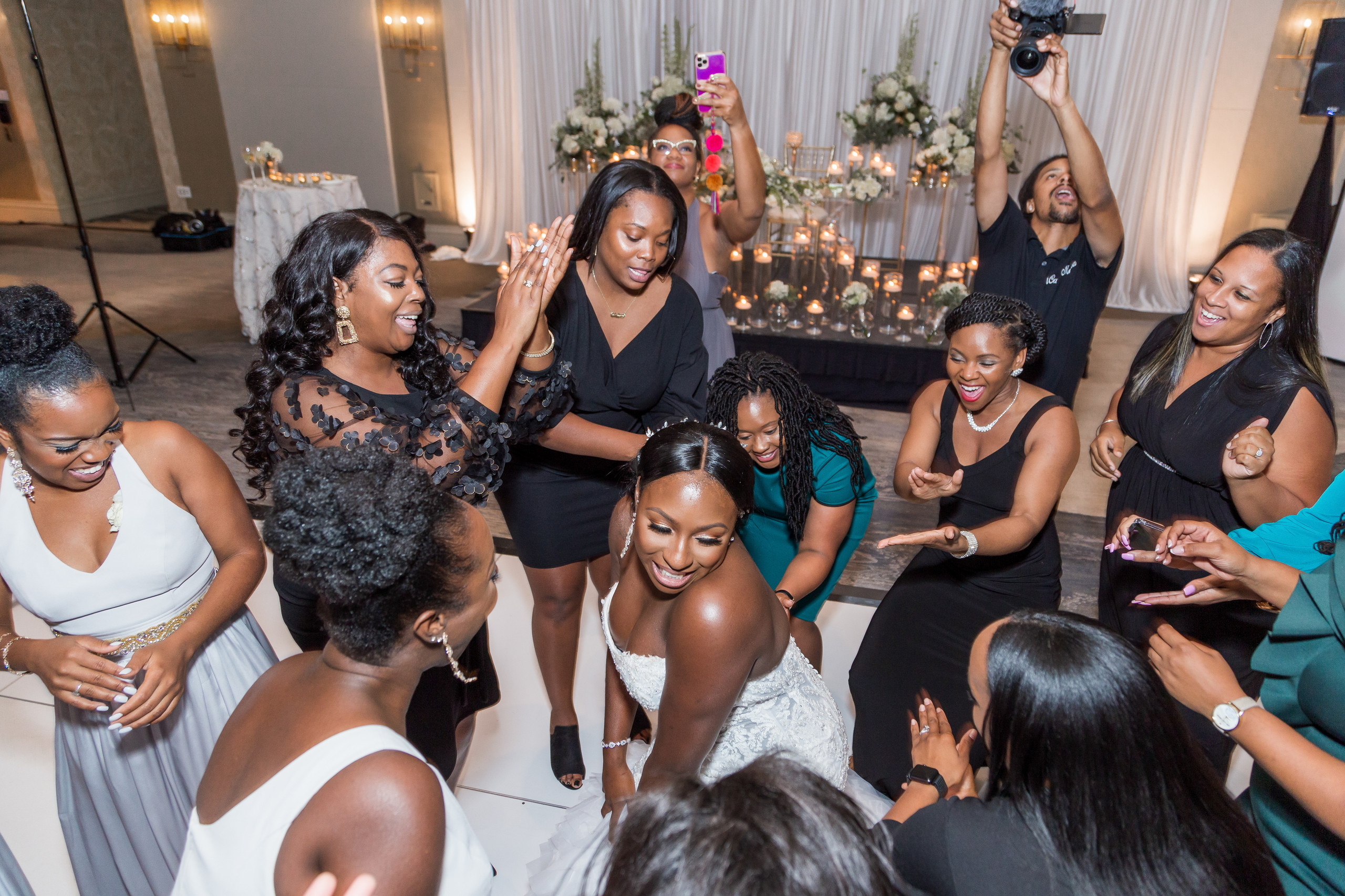 The bride happily dances on the dancefloor with her friends during the wedding reception at the Hilton Main in Norfolk, Virginia.