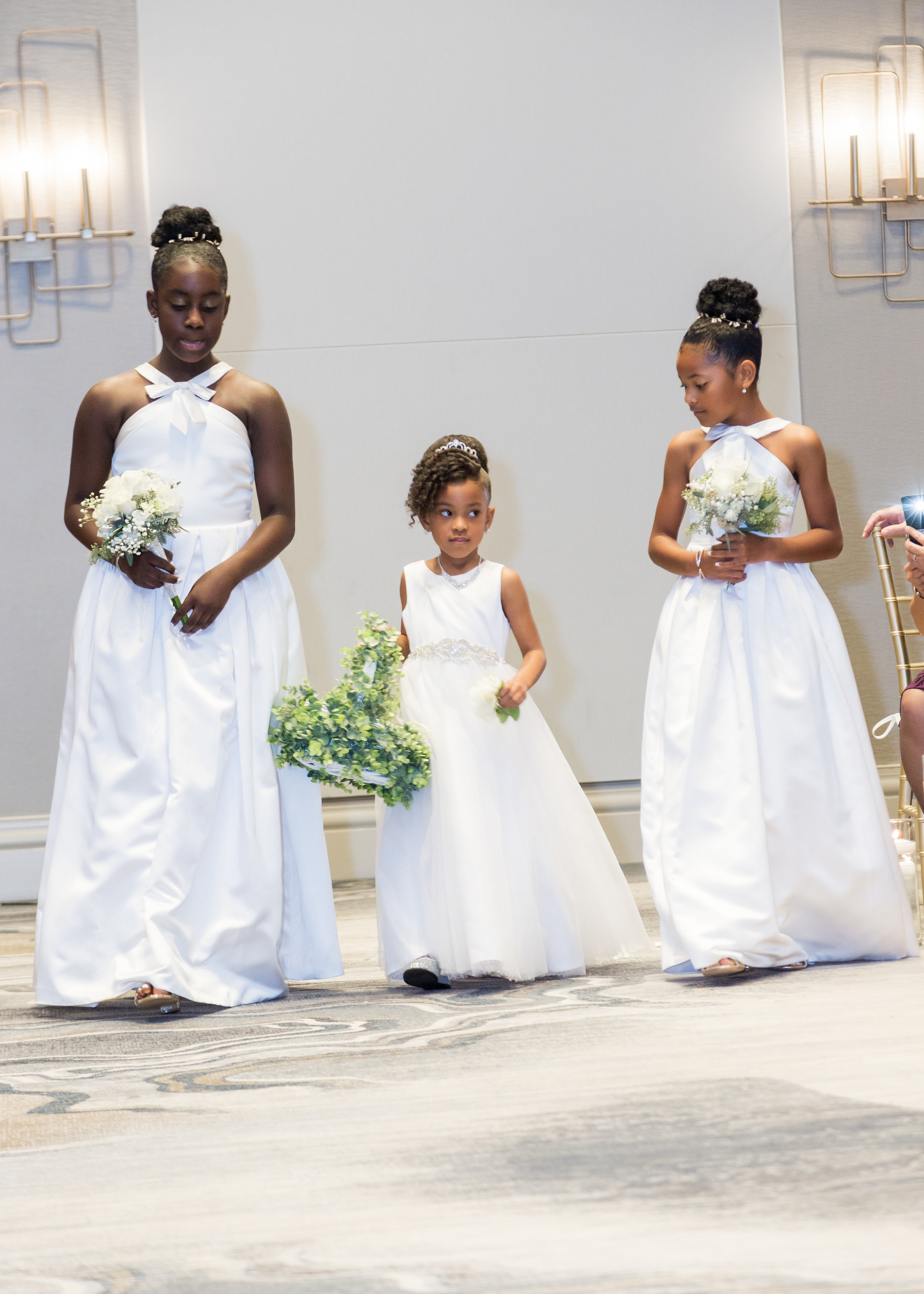 The junior bridesmaids and flower girl come down the isle together during the wedding ceremony at the Hilton Main in Norfolk, Virginia.