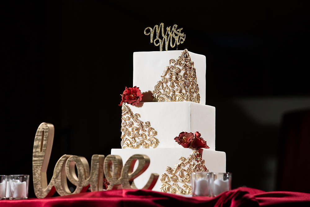 Elegant wedding cake with gold and red accents during the wedding reception at Martin's Crosswinds in Greenbelt, Maryland.