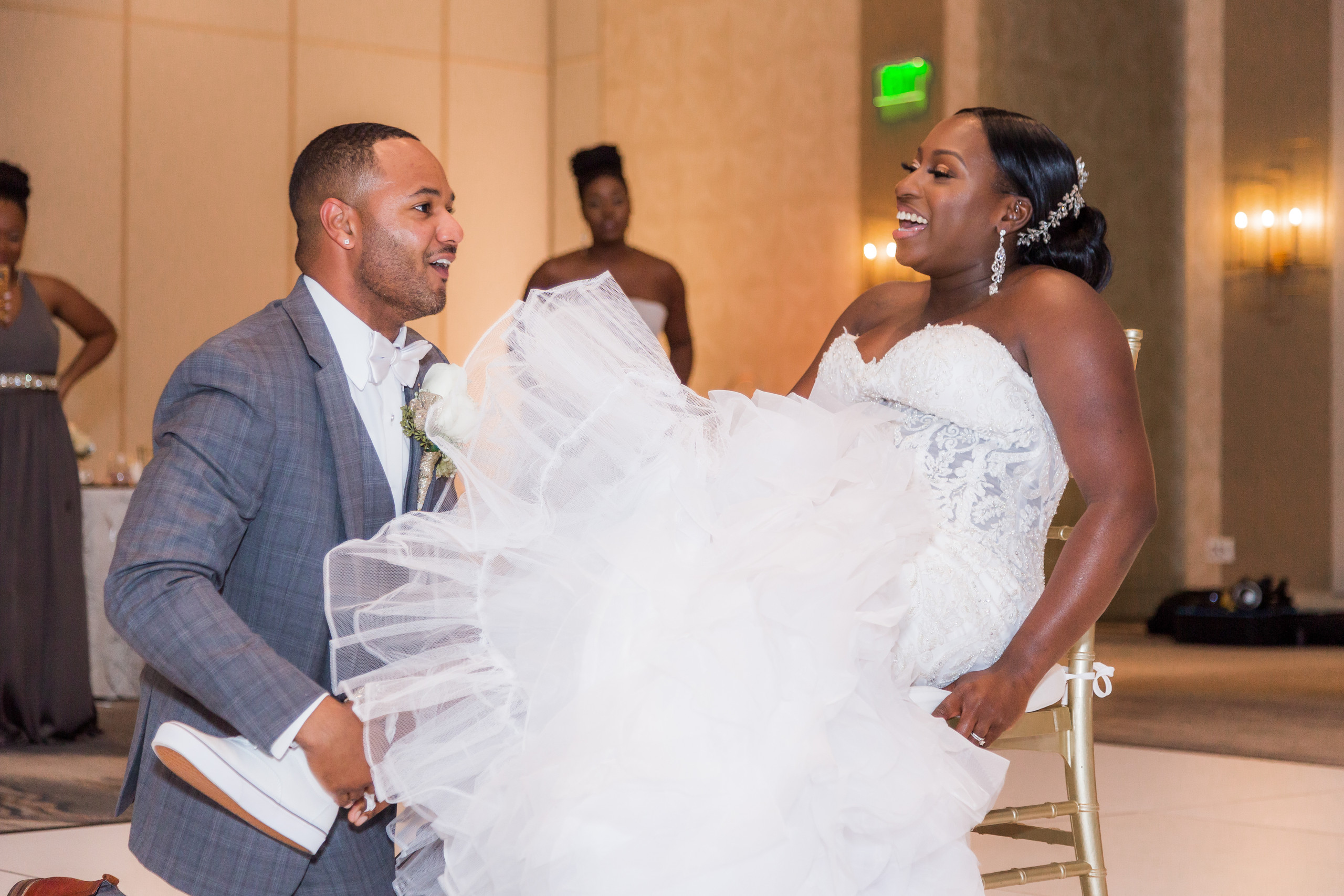 The groom removing the bride's garter to her delight during the wedding reception at the Hilton Main in Norfolk, Virginia.