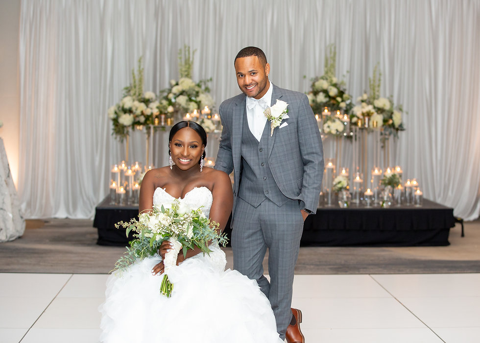 Bride holding her bouquet with groom posing for a portrait in front of their sweetheart table at their wedding reception in Norfolk, Virginia.