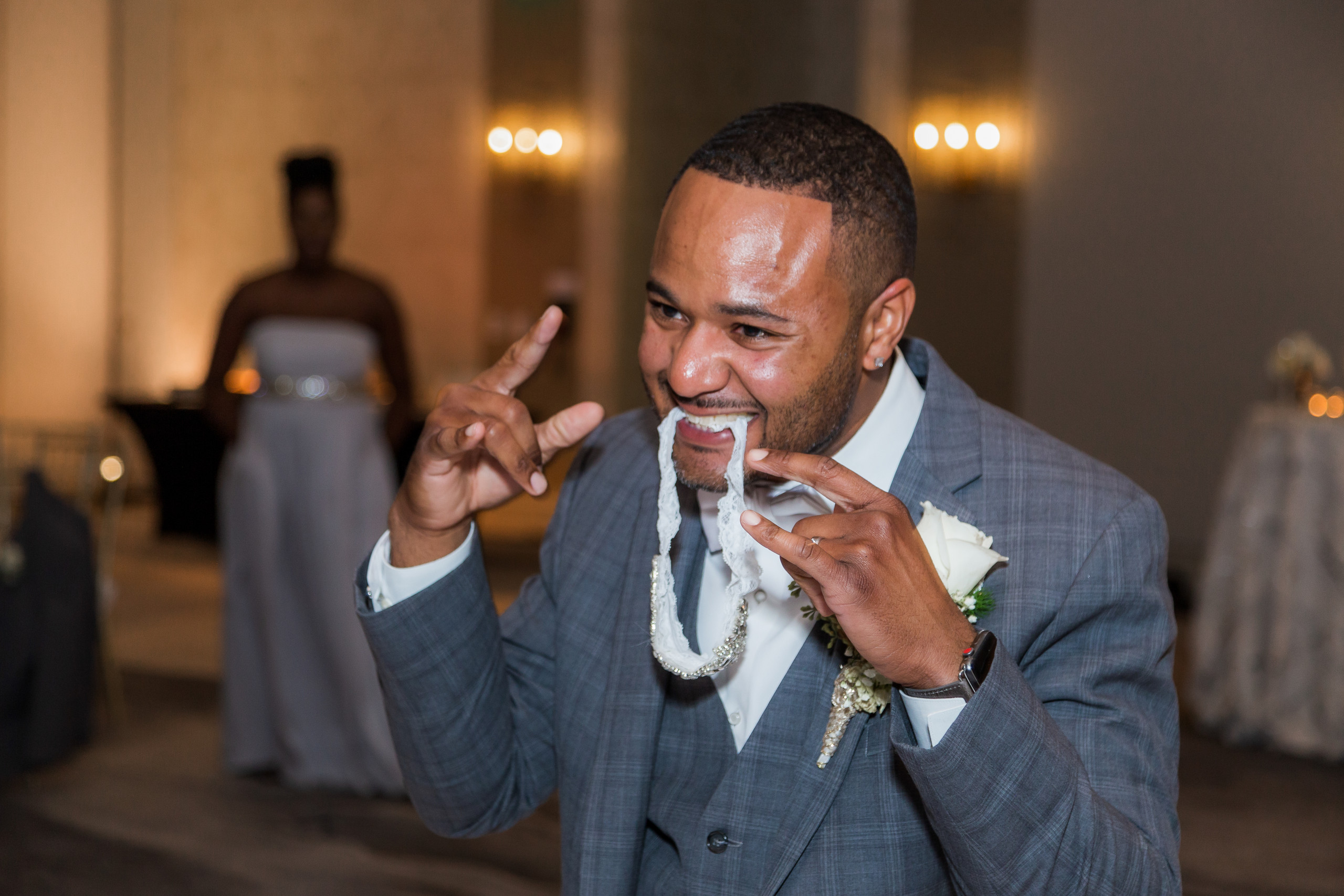 The groom playfully posing with the bride's garter during the wedding reception at the Hilton Main in Norfolk, Virginia.