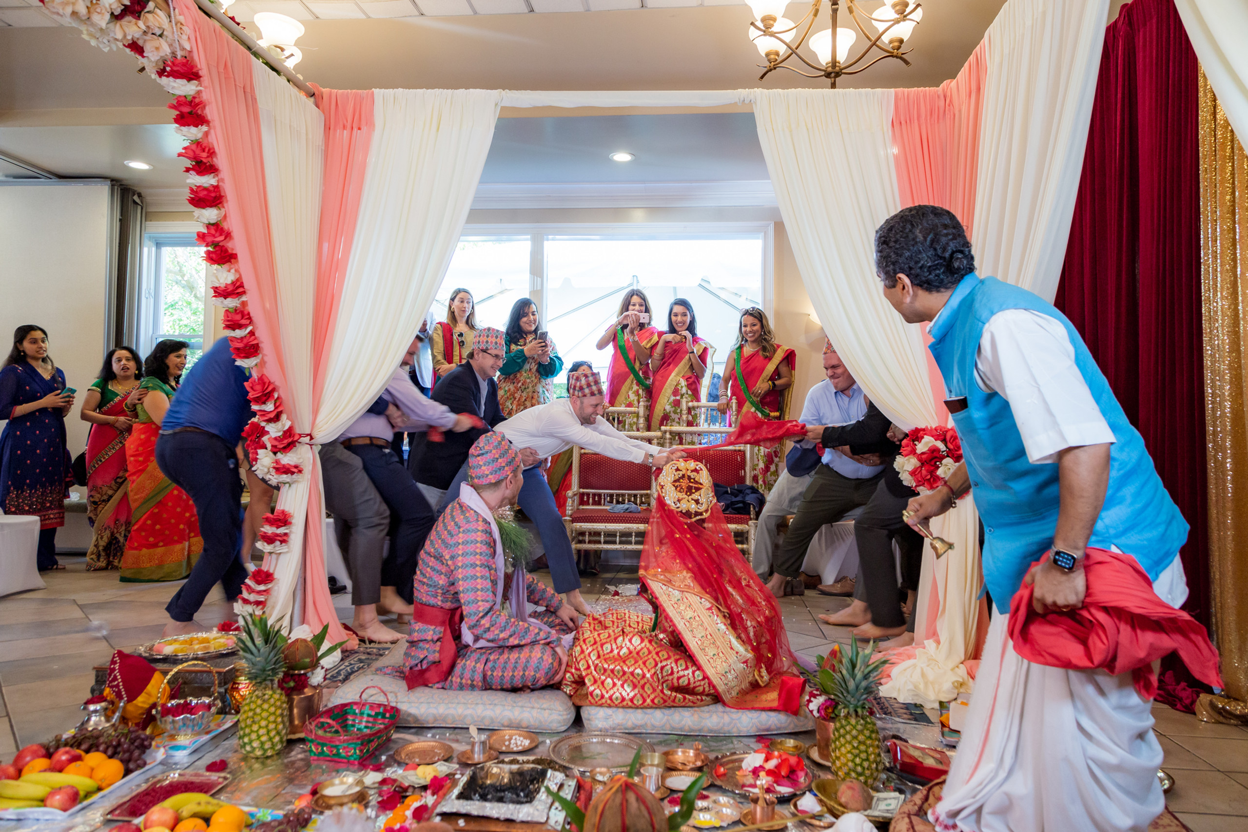 A tug-of-war style wedding ritual between men from both families during the Hindu Ceremony at the ISKCON of DC in Potomac, Maryland.