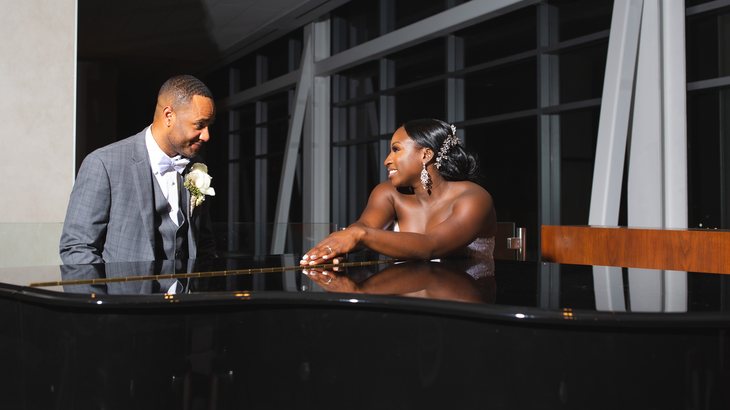 The bride and groom pose for a portrait at a piano during the wedding reception at the Hilton Main in Norfolk, Virginia.