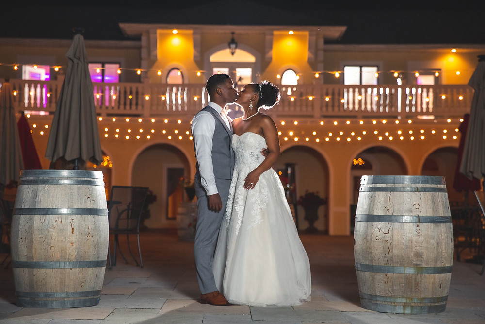 The bride and groom share a special kiss in the night in front of the winnery after the wedding reception at Crosskeys Vineyards in Mt. Crawford, Virginia.