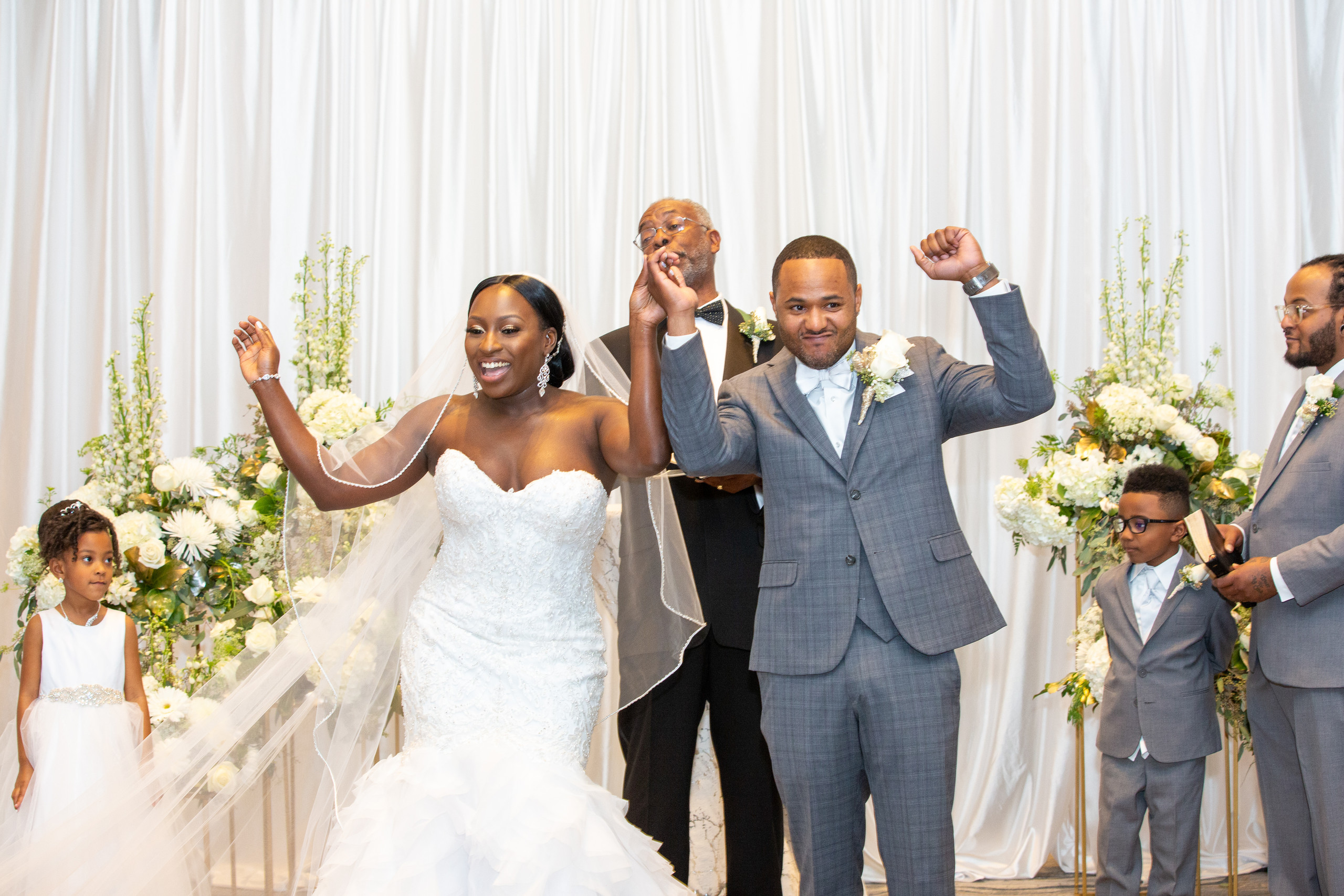 The bride and groom celebrate as the begin the recessional during the the wedding ceremony at the Hilton Main in Norfolk, Virginia.