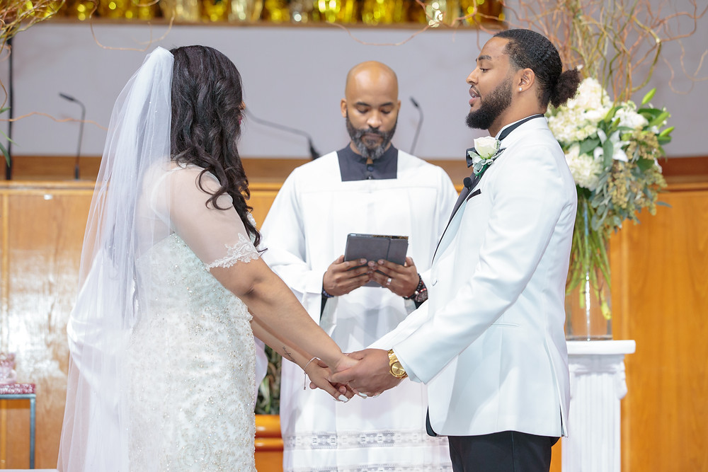 The bride and groom hold hands at the alter as they share their vows with one another at the Alfred Street Baptist Church in Alexandria, Virginia.