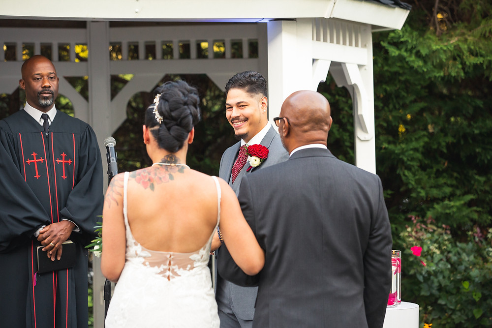 Bride meeting the groom at the alter during the wedding ceremony at Martin's Crosswinds in Greenbelt, Maryland.