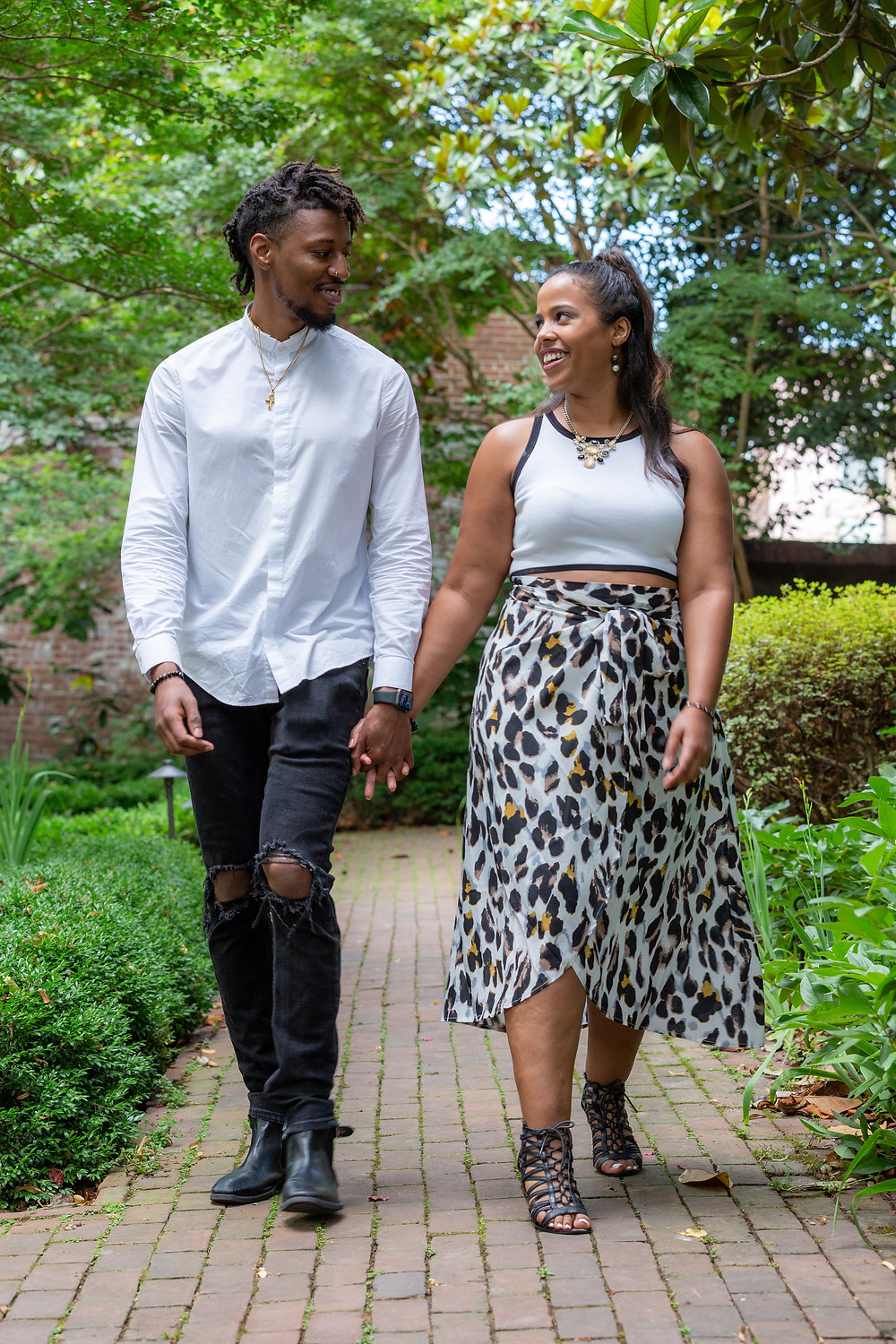 Couple holding hands during their engagement session at The Carlyle House in Old Town Alexandria, Virginia.