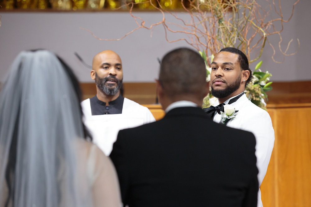 The groom watches on as his bride approaches the alter with her father at the Alfred Street Baptist Church in Alexandria Virginia.