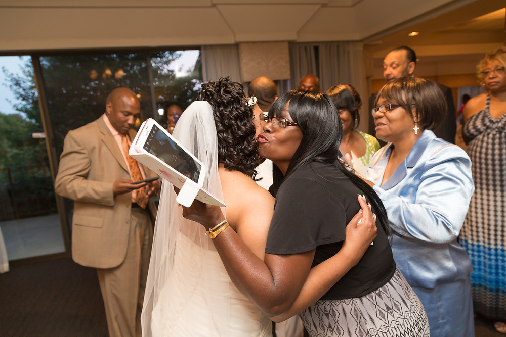 Guest hugging the bride while holding a tablet.