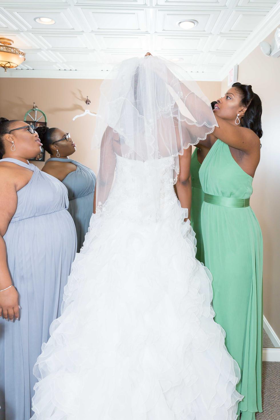 Bridesmaids helping the bride.