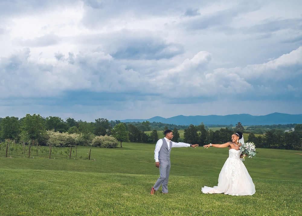 The bride and groom pose for a portrait in a field after the wedding ceremony at Crosskeys Vineyards in Mt. Crawford, Virginia.