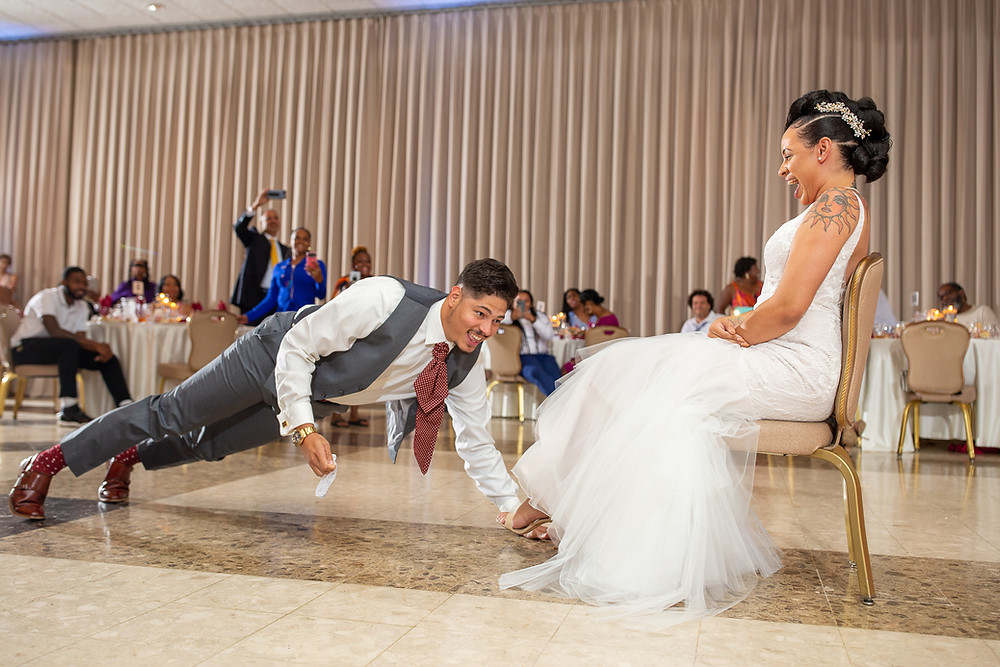 The groom put on quite a show while retrieving the bridal garter during the wedding reception at Martin's Crosswinds in Greenbelt, Maryland.