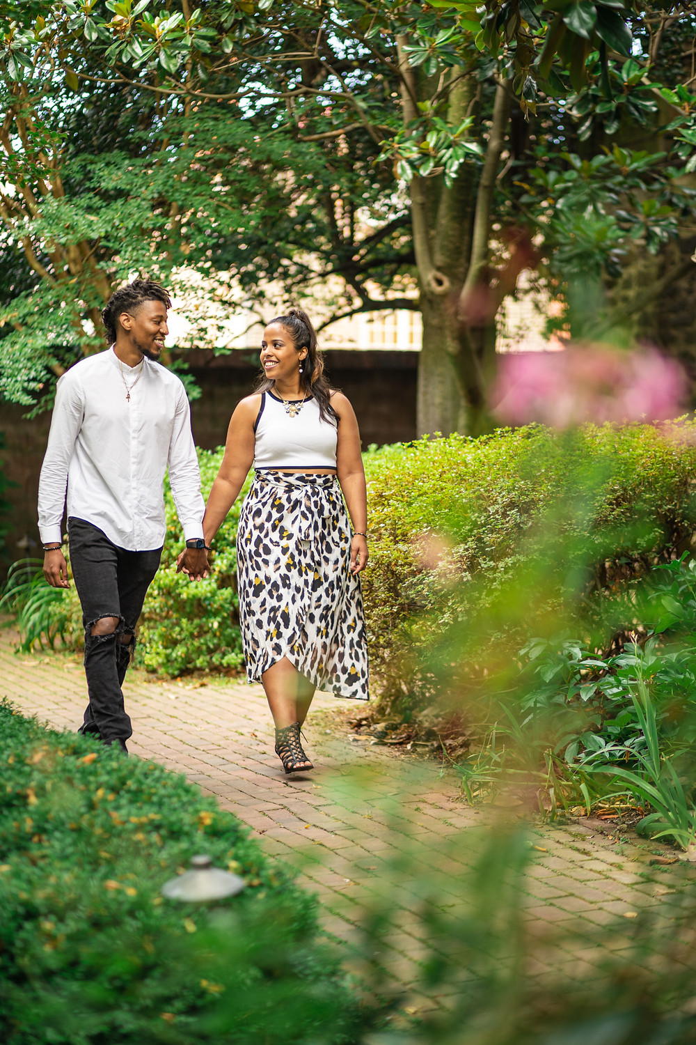 Couple walking in the garden during their engagement session at The Carlyle House in Old Town Alexandria, Virginia.