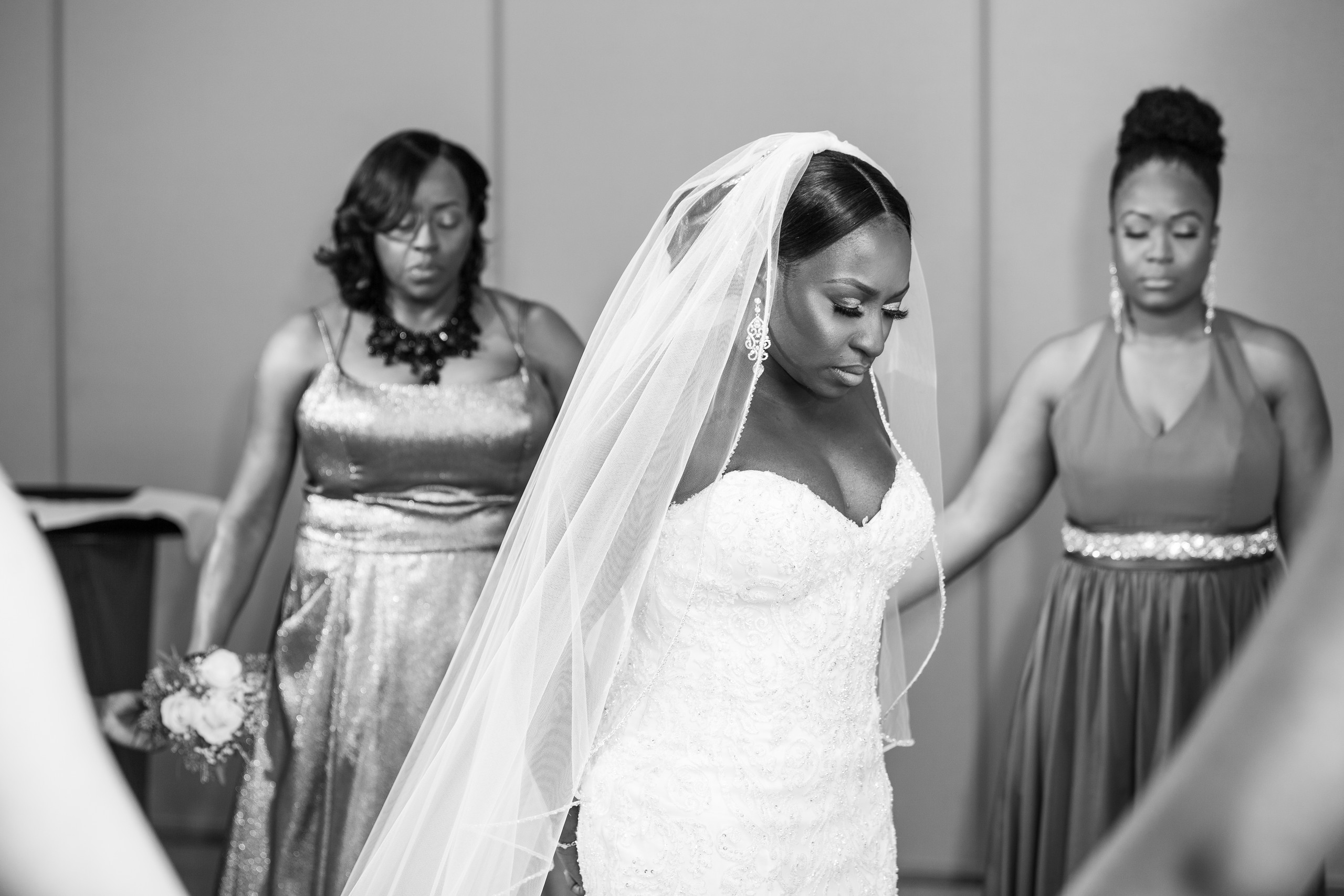 Bride praying with her family and bridal party before the wedding ceremony at the Hilton Main in Norfolk, Virginia.