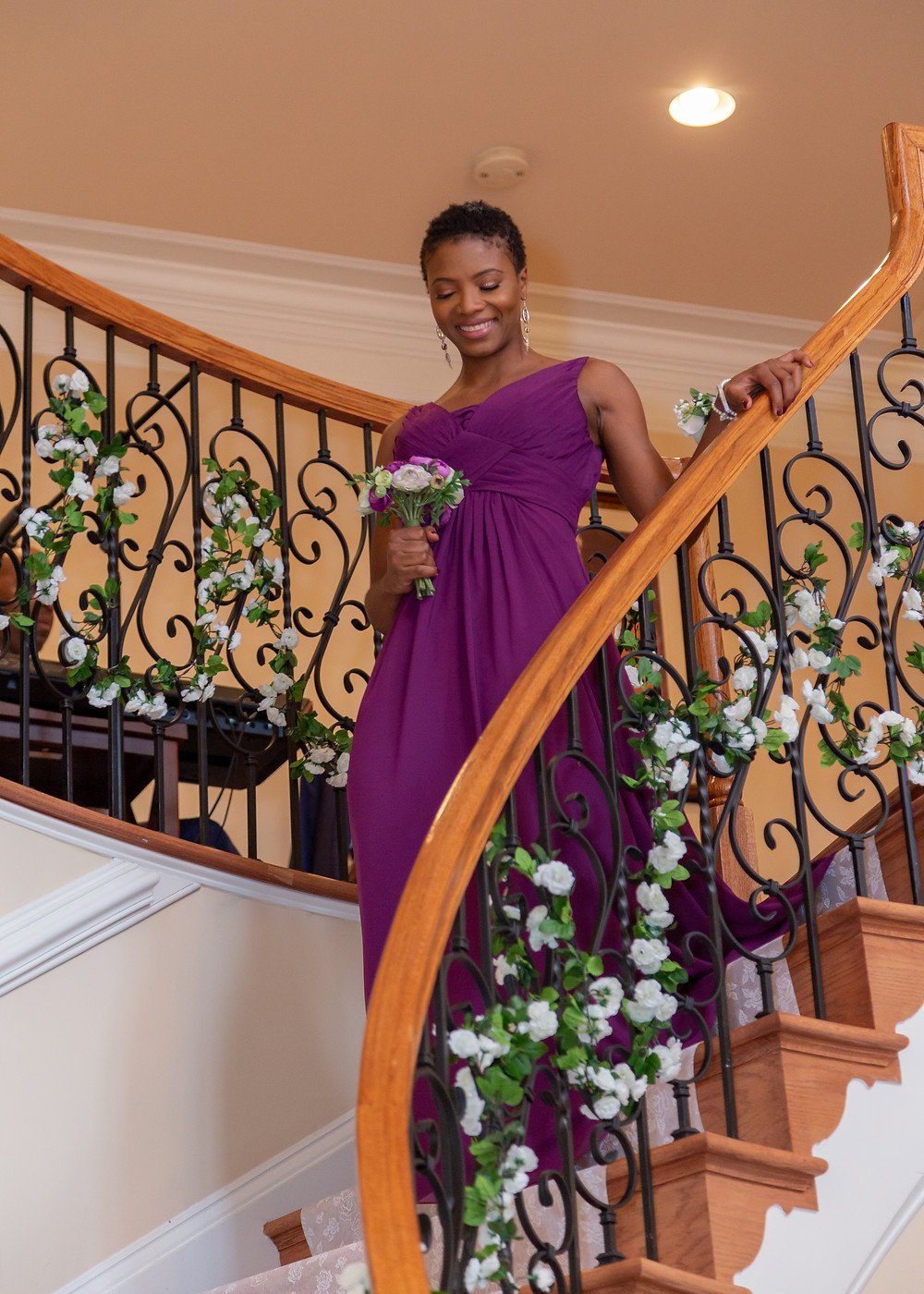 A bridesmaid walking down the stairs into the ceremony in Fairfax, Virginia.