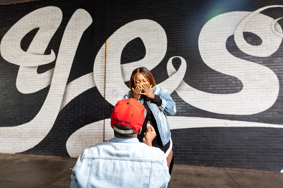 Christopher proposing to Jade by the Yes Wall in Dumbo Brooklyn, New York.
