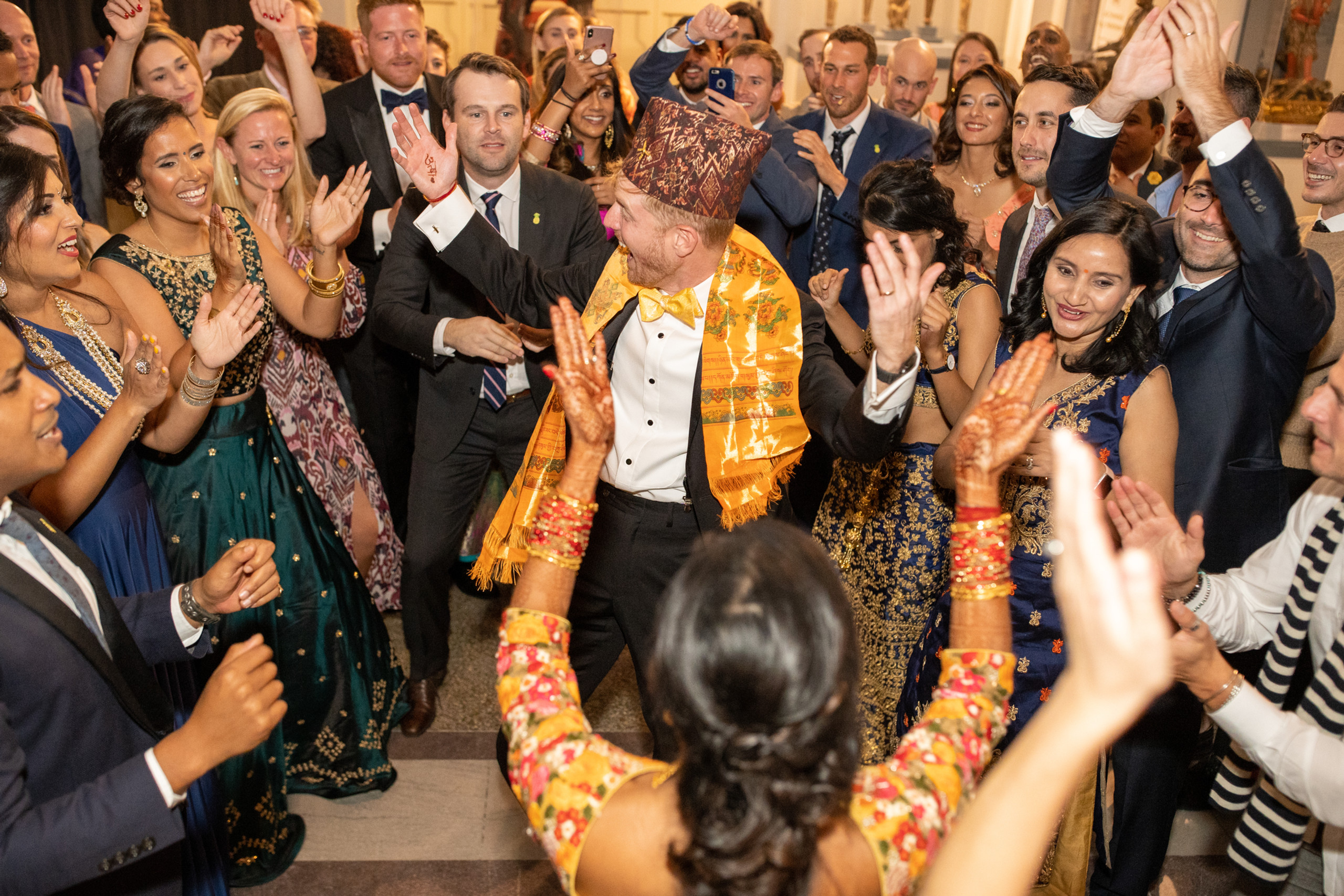 The bride and groom join in the flashmob during the wedding reception at the Penn Museum in Philadelphia, Pennsylvania.