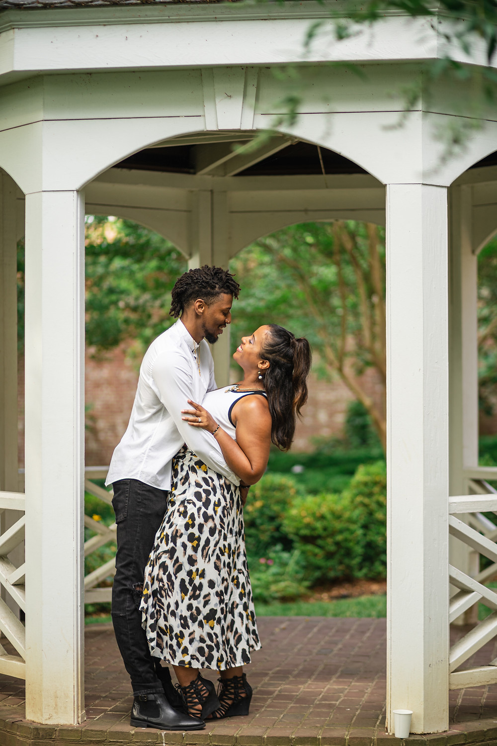 Couple dancing in the garden at their engagement session at The Carlyle House in Old Town Alexandria, Virginia.