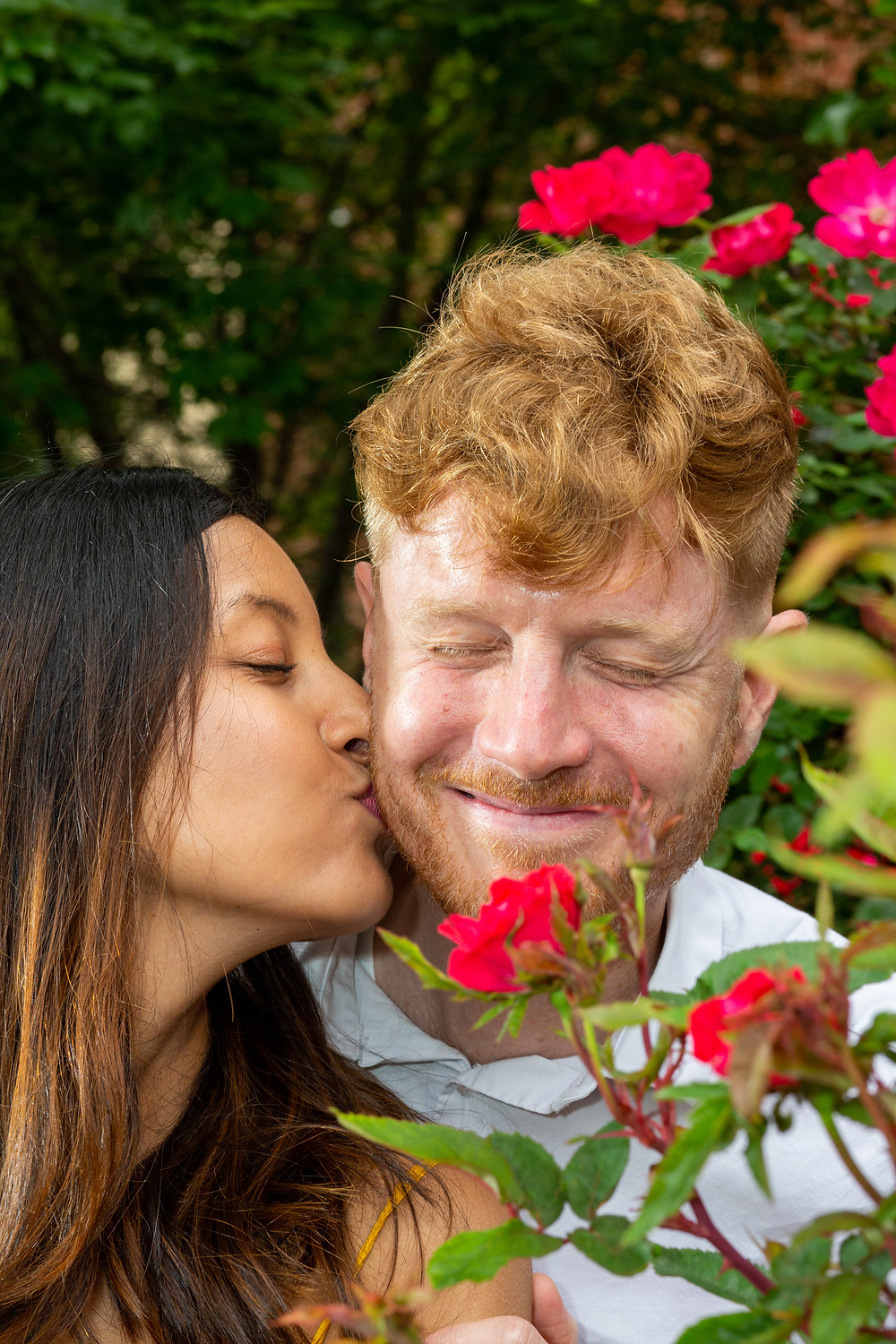 John and UK playfully share an adorable kiss in the rose bushes during the engagement session in Northwest Washington DC.
