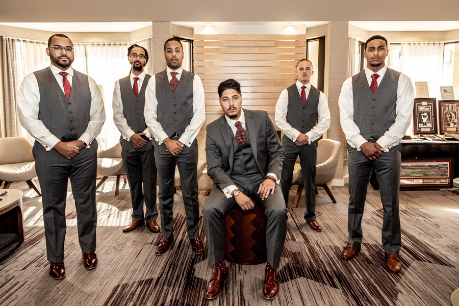 Groom and groomsmen pose for a portrait in the hotel lobby at the Courtyard by Marriott before the wedding ceremony in Greenbelt, Maryland.