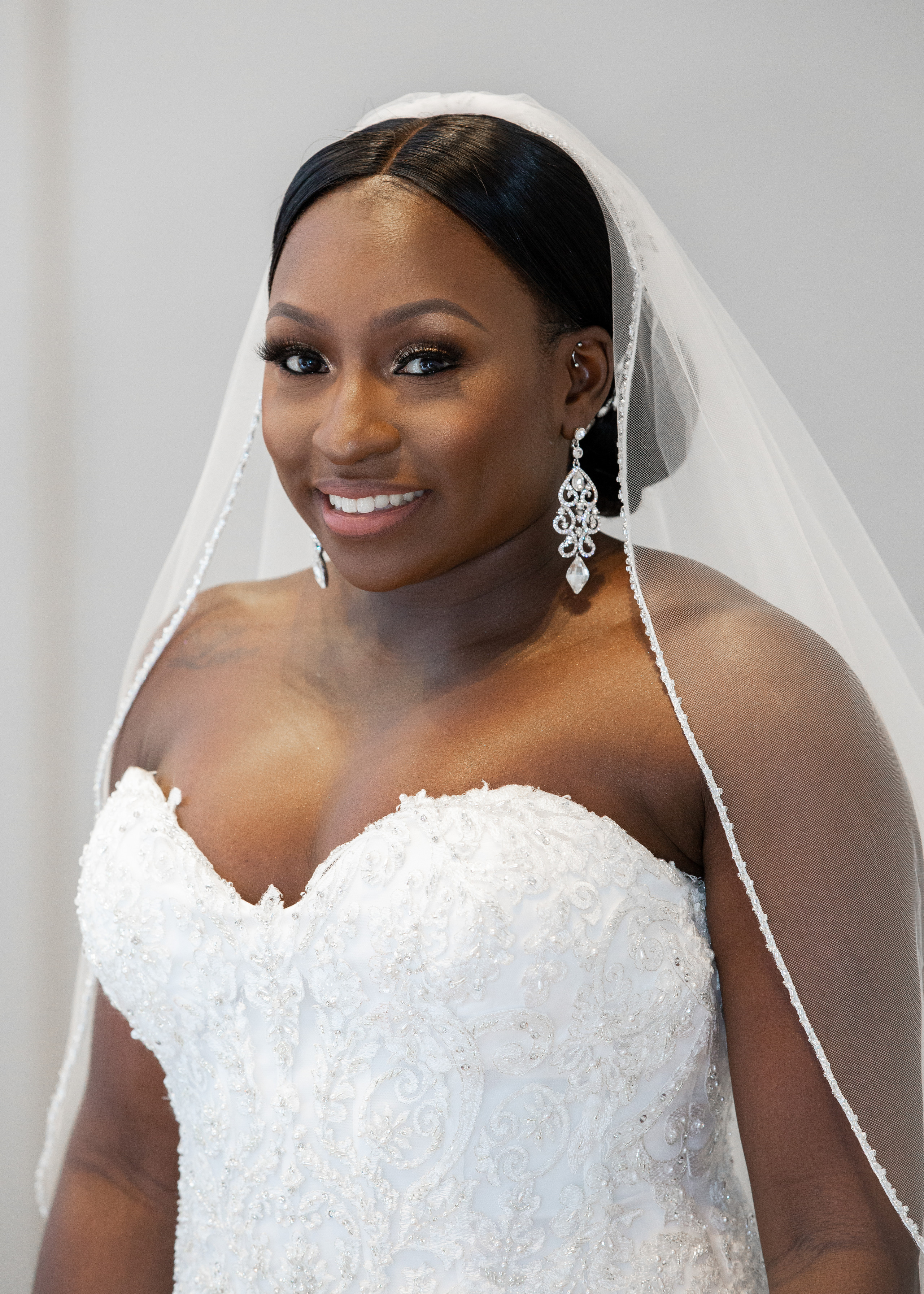 Bridal posing for a portrait showing off her wedding dress, bridal jewelry and wedding day makeup before the wedding ceremony at the Hilton Main in Norfolk, Virginia.