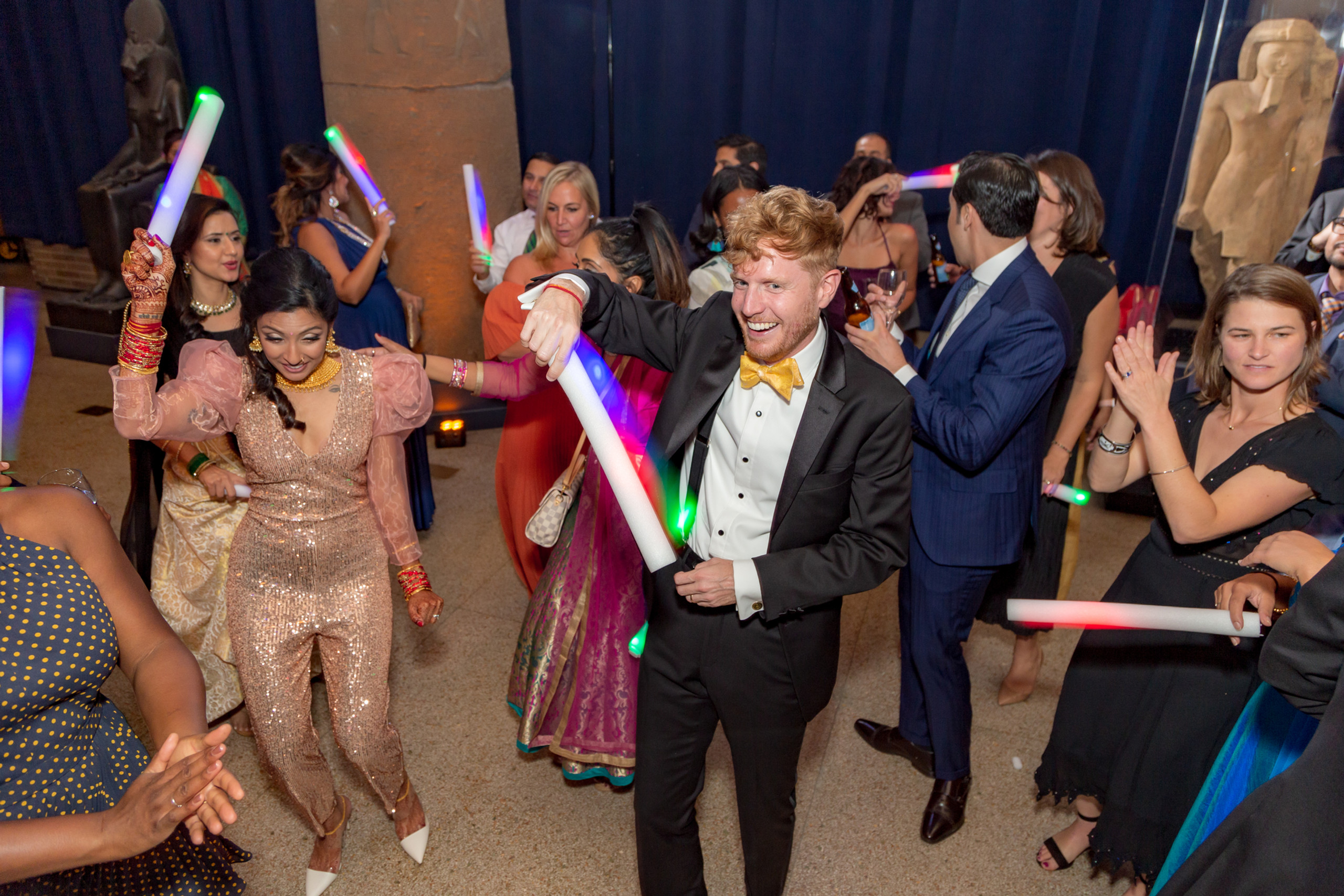 The bride and groom waving their glow sticks on the dance floor during the wedding reception at the Penn Museum in Philadelphia, Pennsylvania.