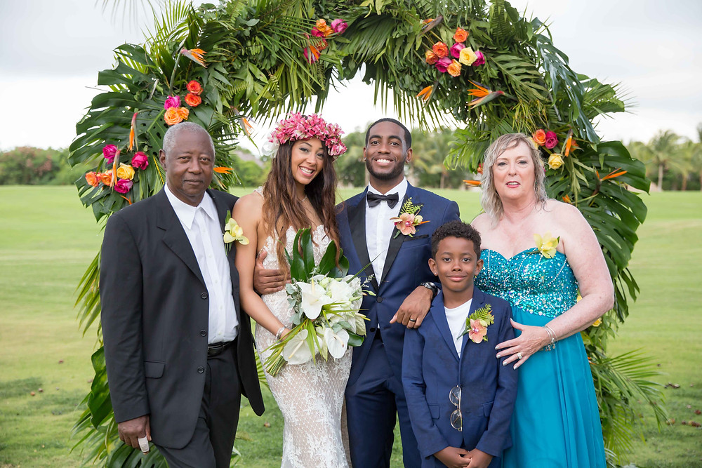 The bride and groom pose for a formal portrait with the family of the bride after the destination wedding in Punta Cana, Dominican Republic