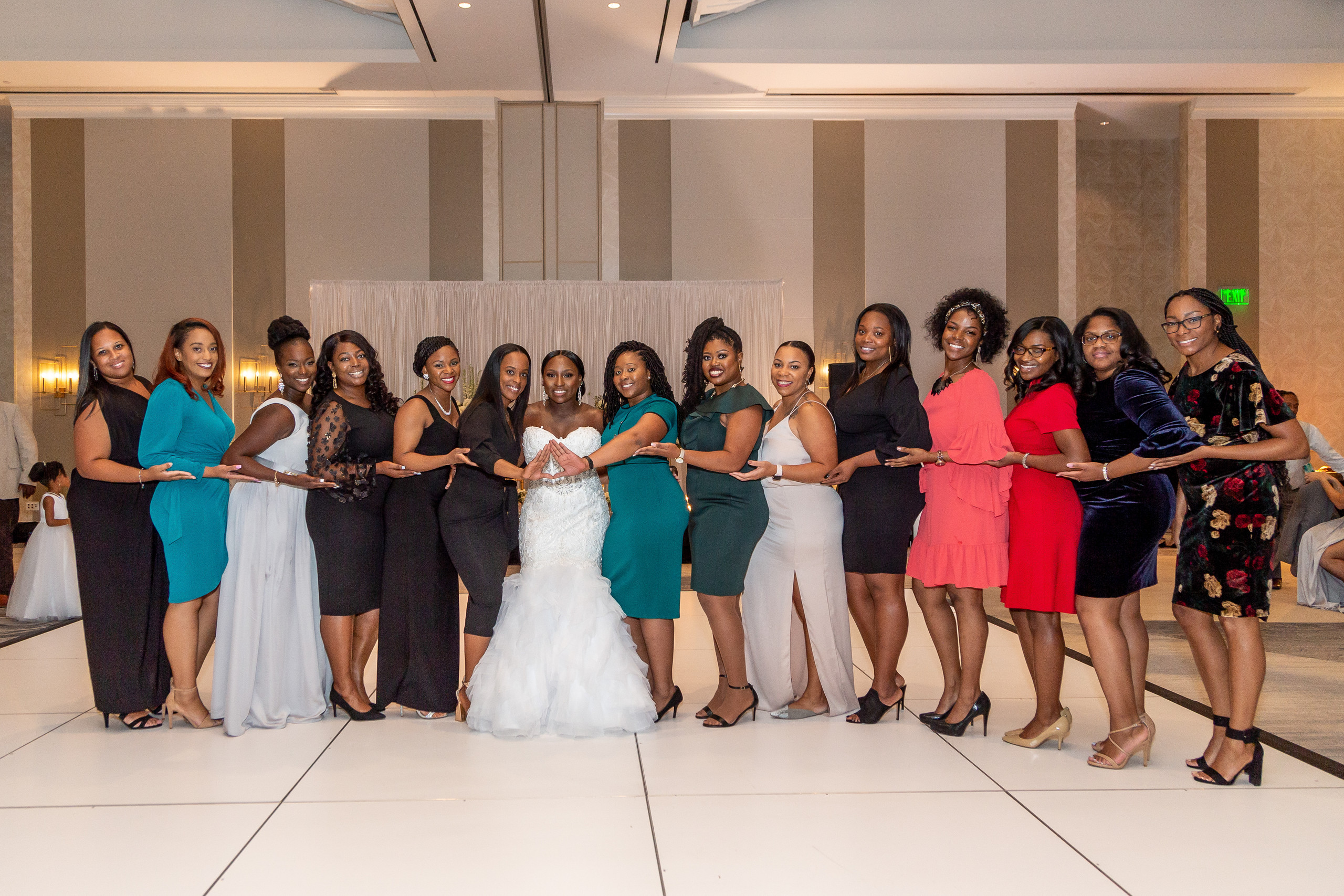 The bride takes a picture with the ladies of Delta Sigma Theta Sorority Incorporated during the wedding reception at the Hilton Main in Norfolk, Virginia.