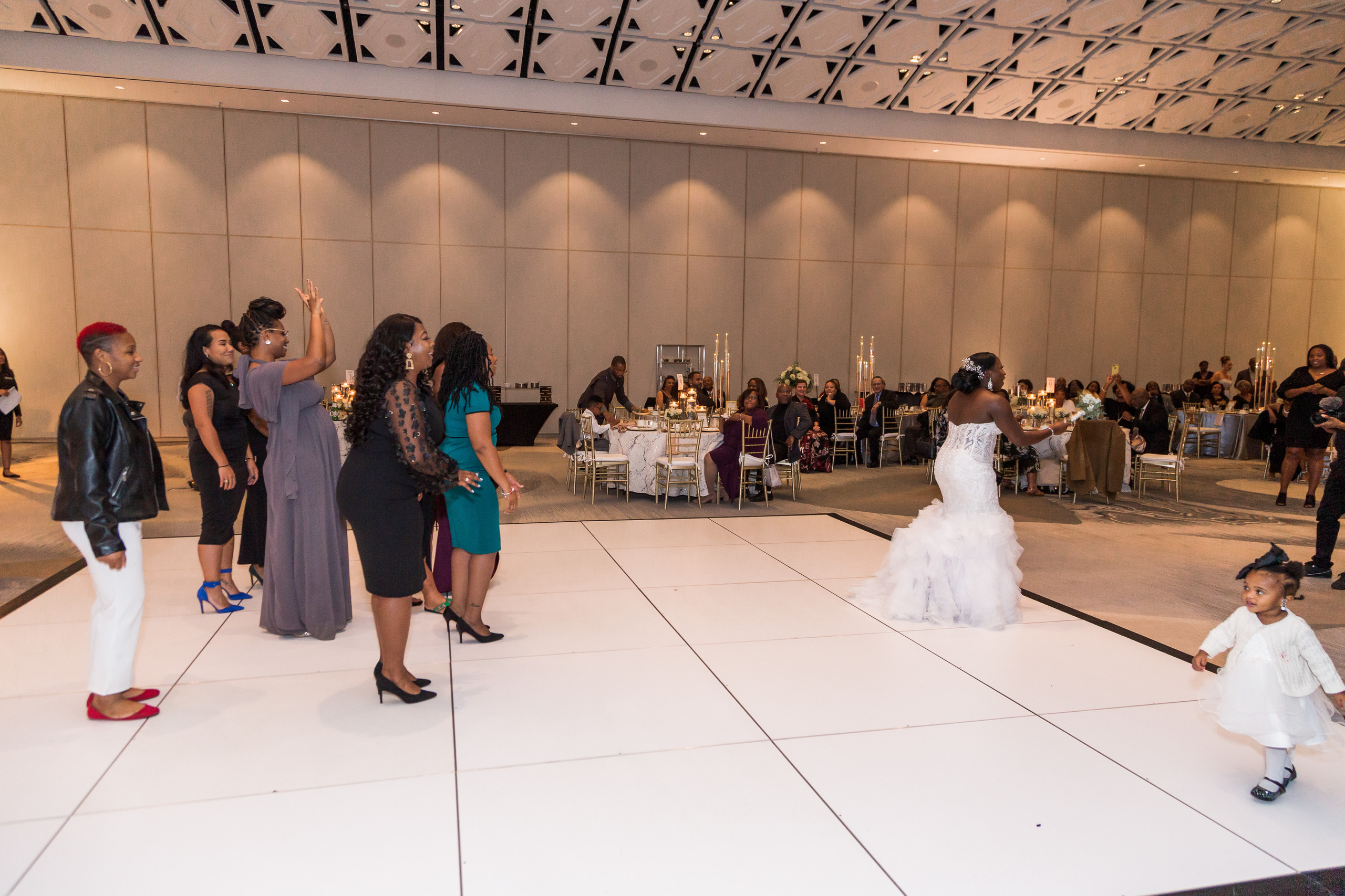 The bride prepares to toss the bouquet during the wedding reception at the Hilton Main in Norfolk, Virginia.