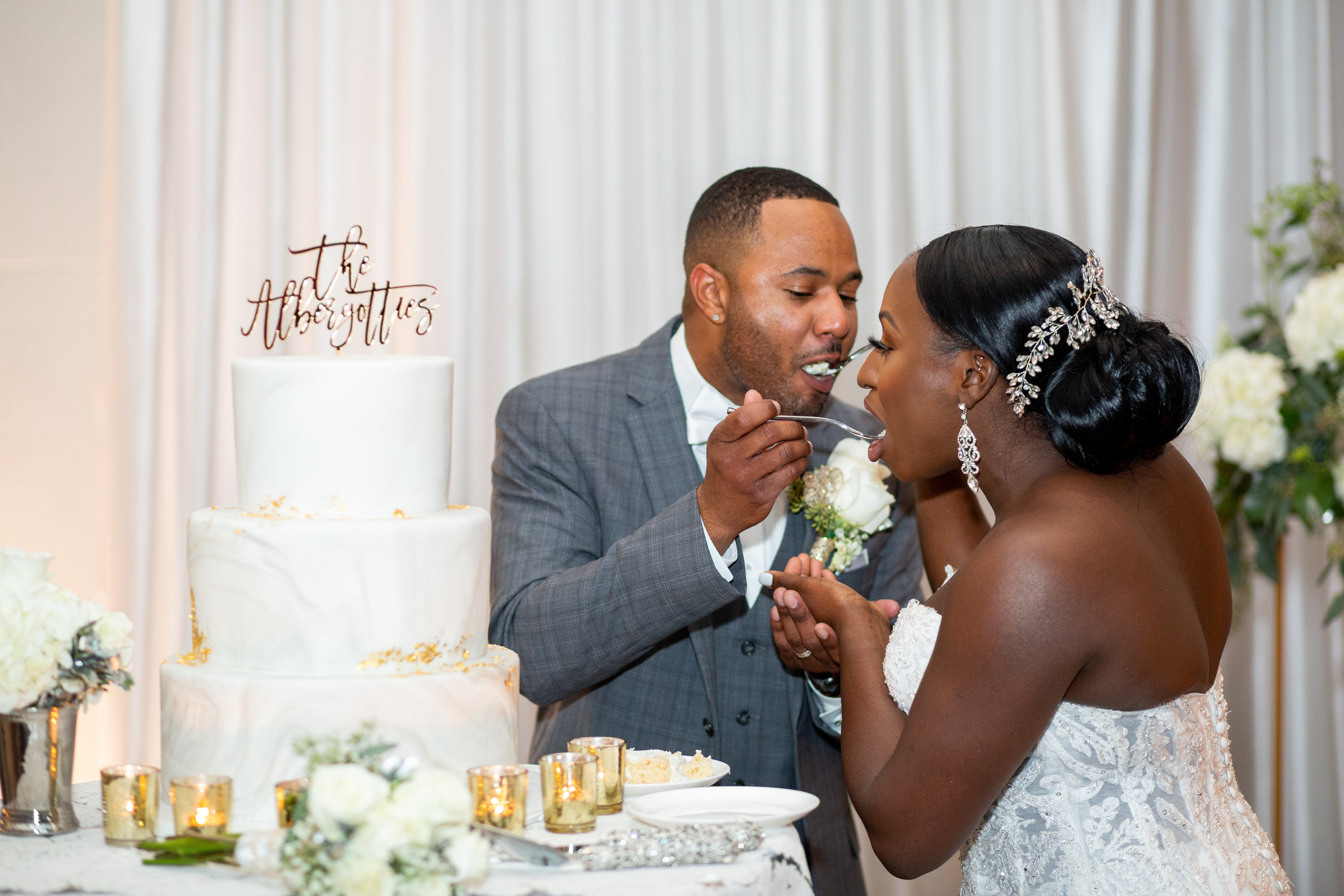 The bride and groom share the first slice of their decadent, classy wedding cake during the wedding reception at the Hilton Main in Norfolk, Virginia.