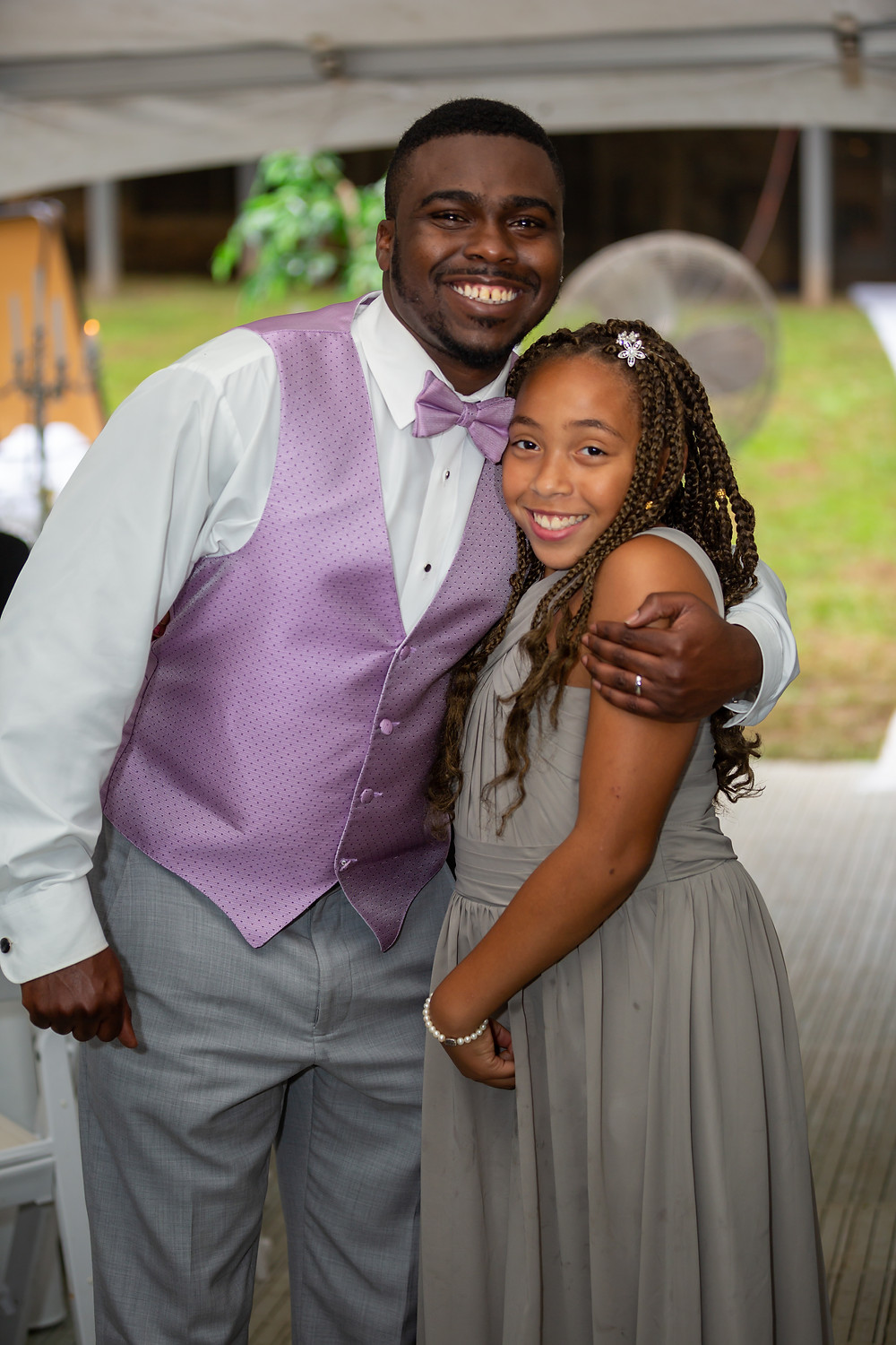 John shares a hug with his flower girl during the wedding reception in Fairfax, Virginia.