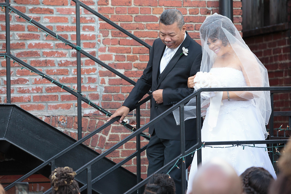 The bride enters the Sellers wedding ceremony with her father/officiant at the Gallery O on H in Washington DC.