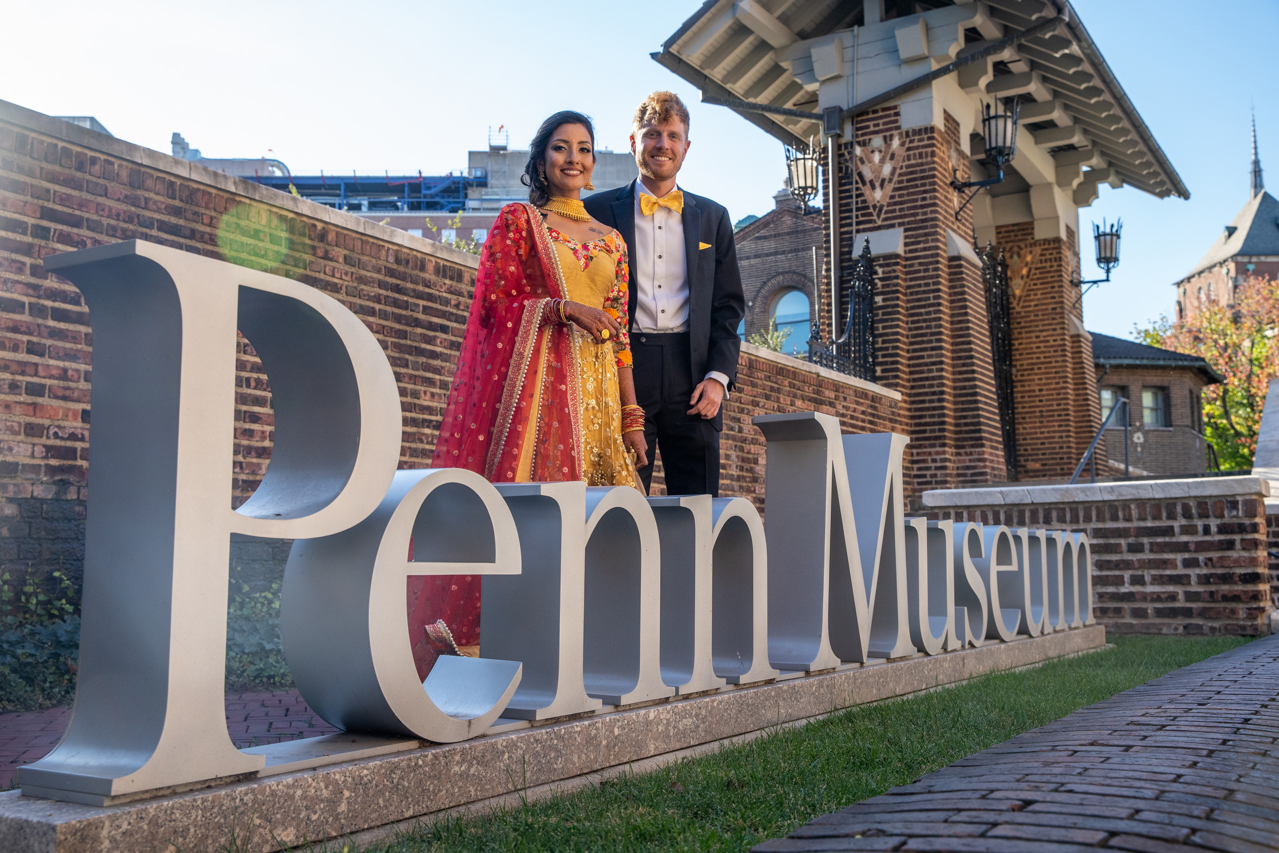 The bride and groom pose in front of the venue sign before the wedding ceremony at the Penn Museum in Philadelphia, Pennsylvania.