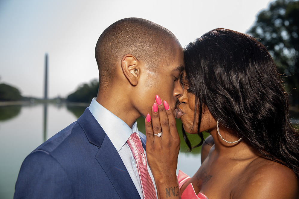 Beyonka and E'an share a kiss while she flashes her diamond engagment ring by the Reflecting Pool in front of the Lincoln Memorial during the engagement session in Washington DC.