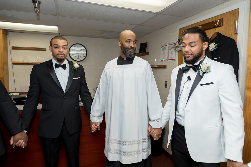 The groom shares a prayer with his groomsmen before the wedding ceremony at the Alfred Street Baptist Church in Alexandria VA.