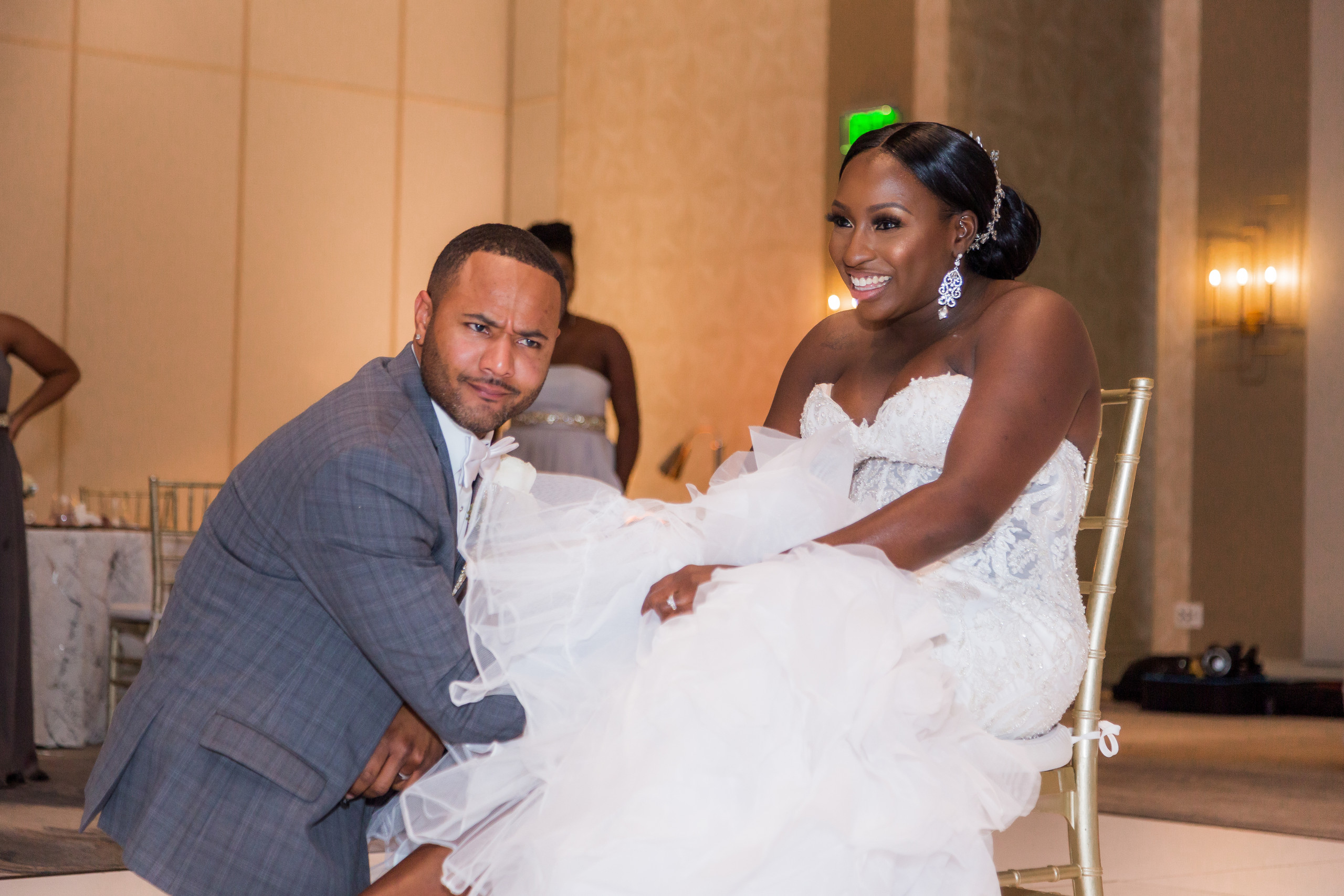 The groom retrieving the bride's garter during the wedding reception at the Hilton Main in Norfolk, Virginia.