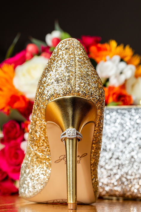 A bride's wedding ring on her golden glitter wedding day heels in front of the bride's wedding day clutch and bridal bouquet.