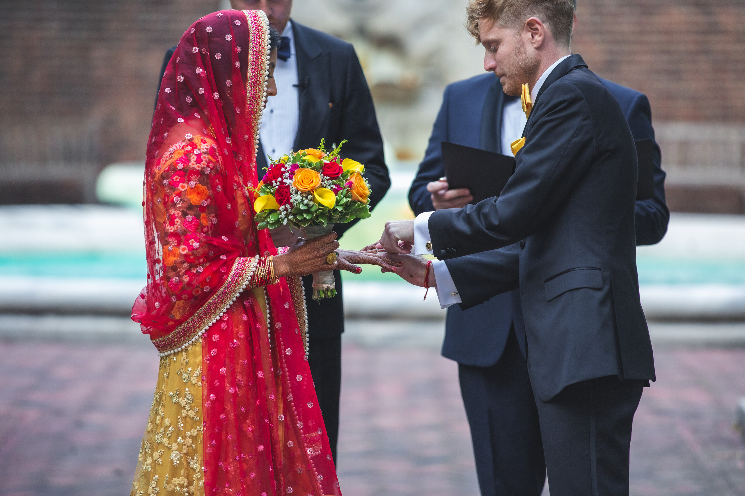 The groom places the bride's wedding band on her hand during the wedding ceremony at the Penn Museum in Philadelphia, Pennsylvania.