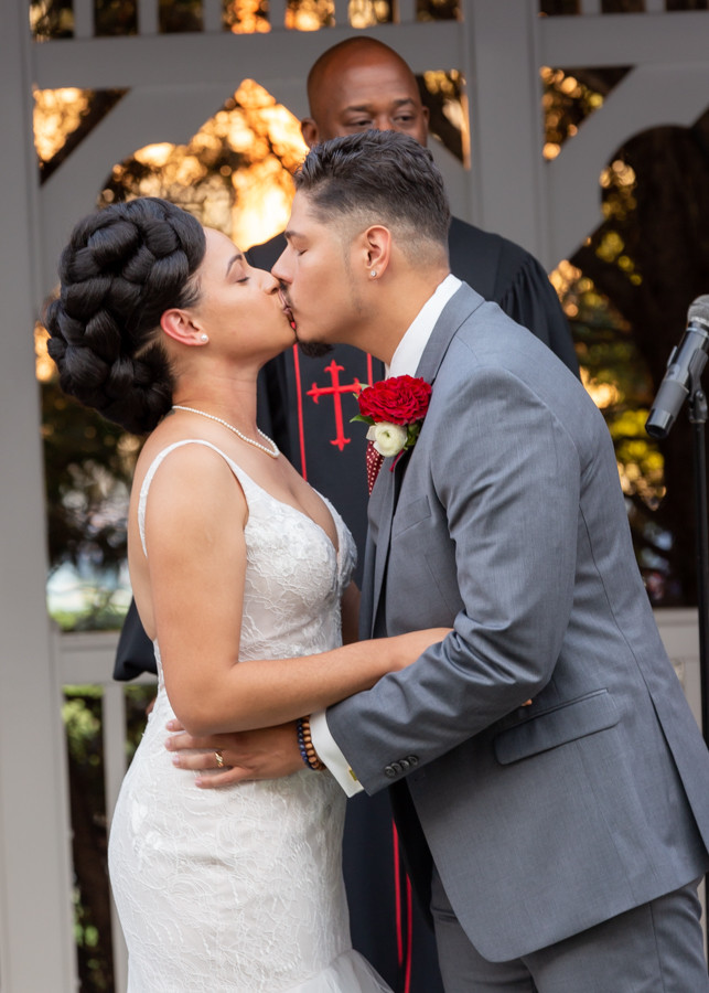 Bride and groom's first kiss during the wedding ceremony at Martin's Crosswinds in Greenbelt, Maryland.