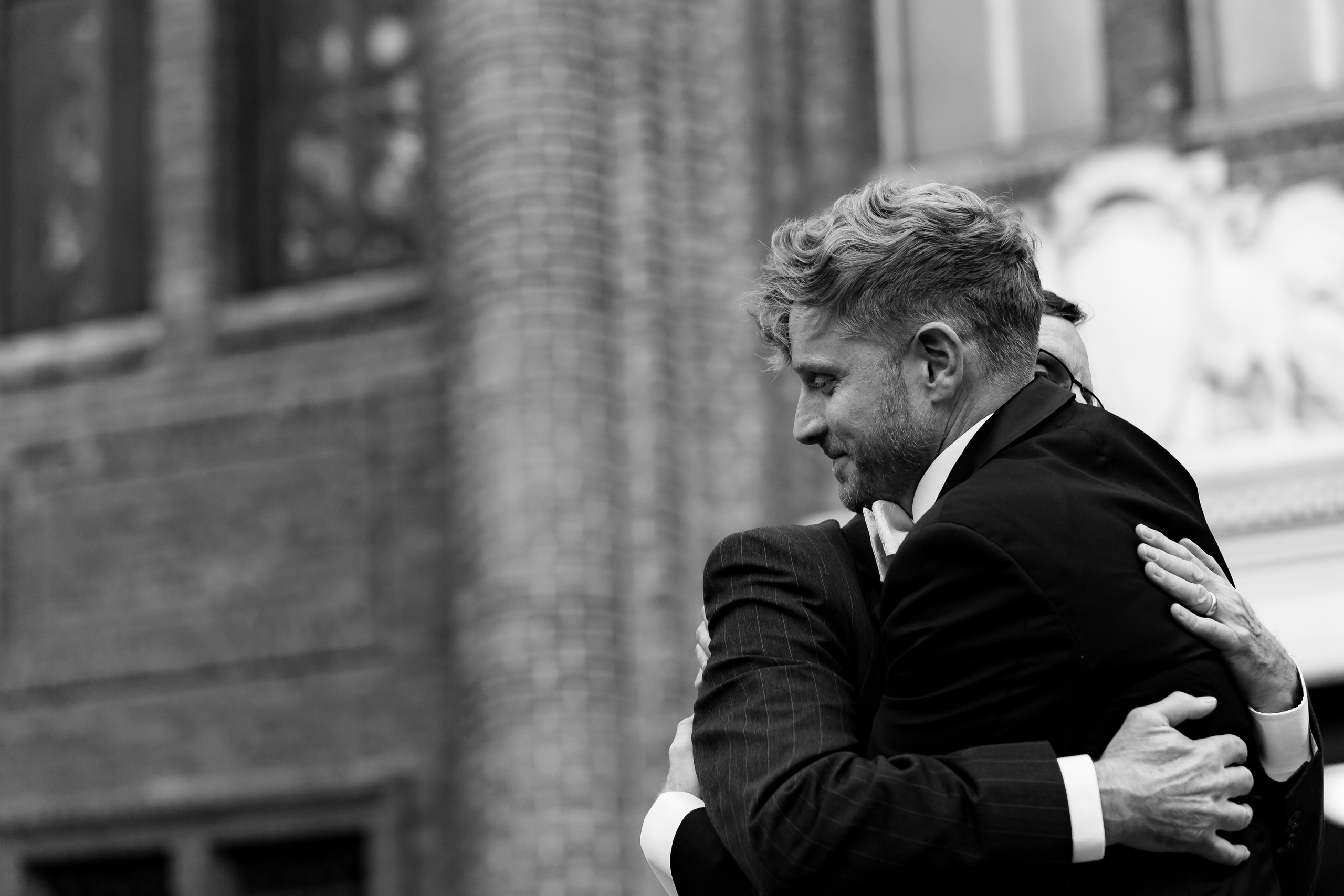 The groom shares a hug with his father during the wedding ceremony at the Penn Museum in Philadelphia, Pennsylvania.