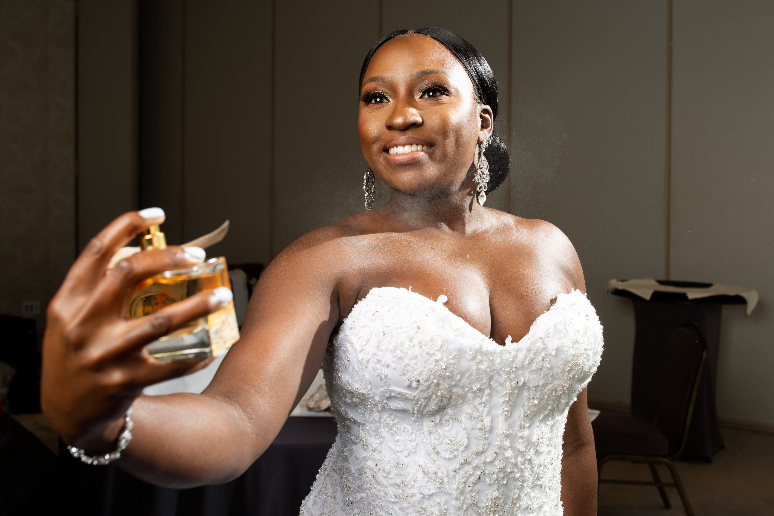 Bride applies her Burberry perfume before the wedding ceremony at the Hilton Main in Norfolk, Virginia.