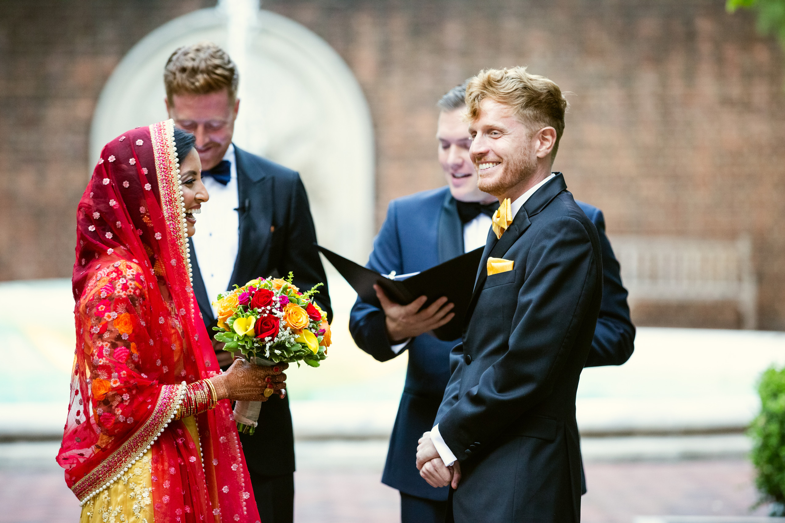 The bride and groom share a laugh during the wedding ceremony at the Penn Museum in Philadelphia, Pennsylvania.