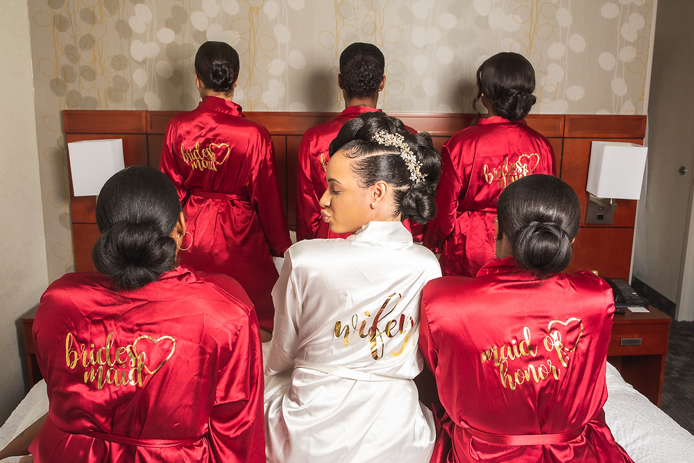 Bride and her bridesmaids showing off their custom bridal robes before the wedding at Martin's Crosswinds in Greenbelt, Maryland.