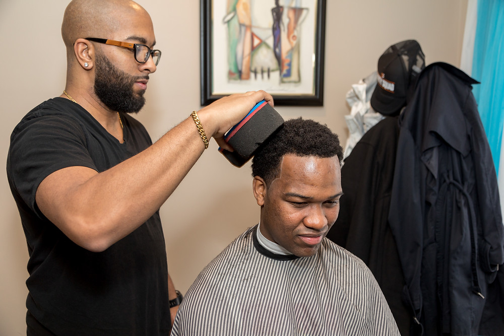 A groomsmen getting a haircut during the wedding preparation in Washington DC.