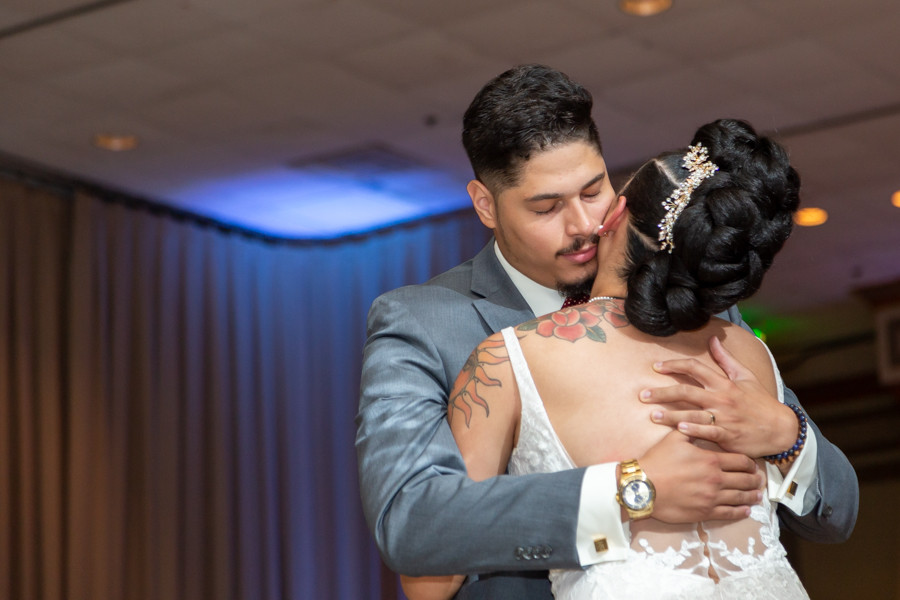 Groom embracing the bride during their first dance during the wedding reception at Martin's Crosswinds in Greenbelt, Maryland.